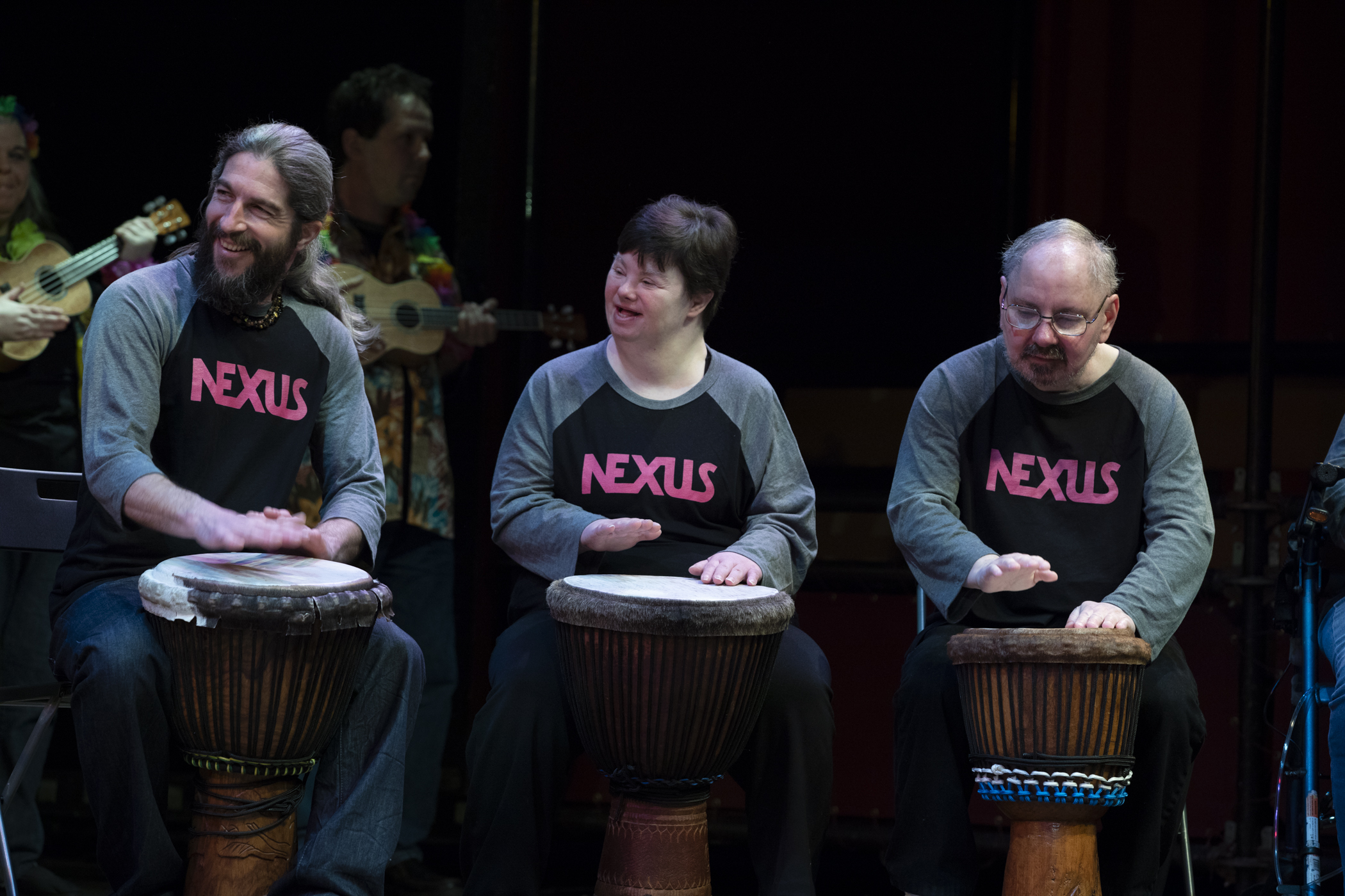 """Three people sit in a row playing drums. They are on stage, smiling, each wearing a shirt that says """"Nexus"""""""