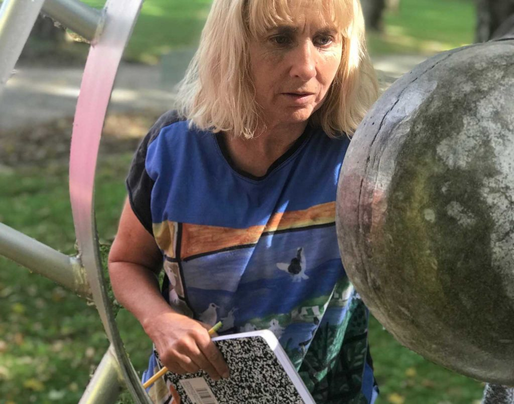 A woman holds a pencil and notebook while looking at a large, metal ball