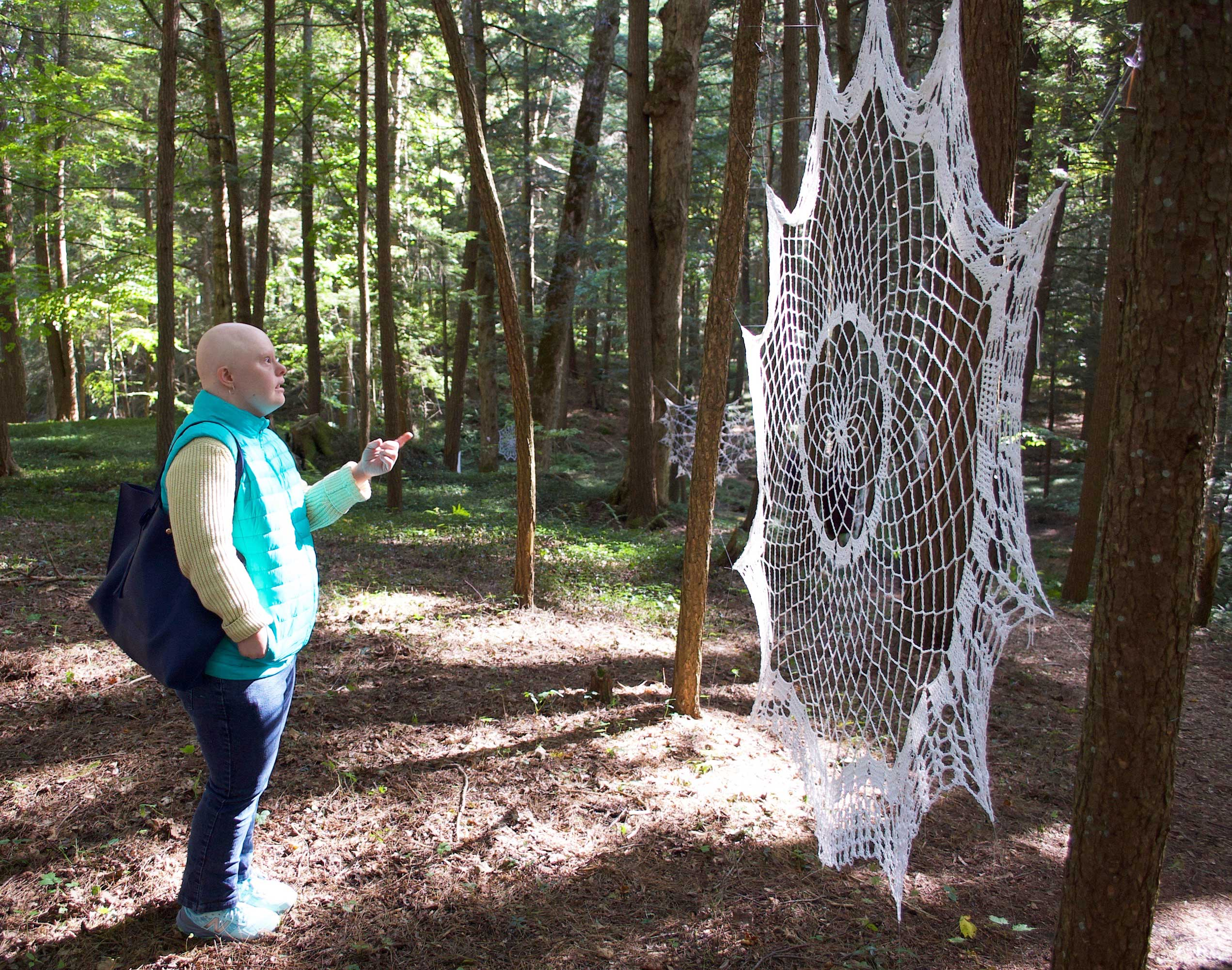 A woman stands outside, pointing to a large, knit, web-like net that is strung in front of her between two trees.