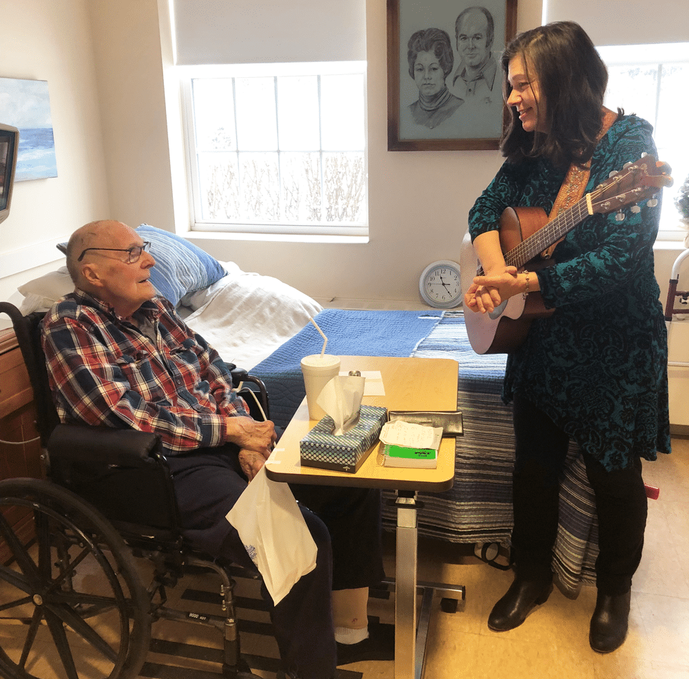 Elder man in a wheelchair with a woman holding a guitar