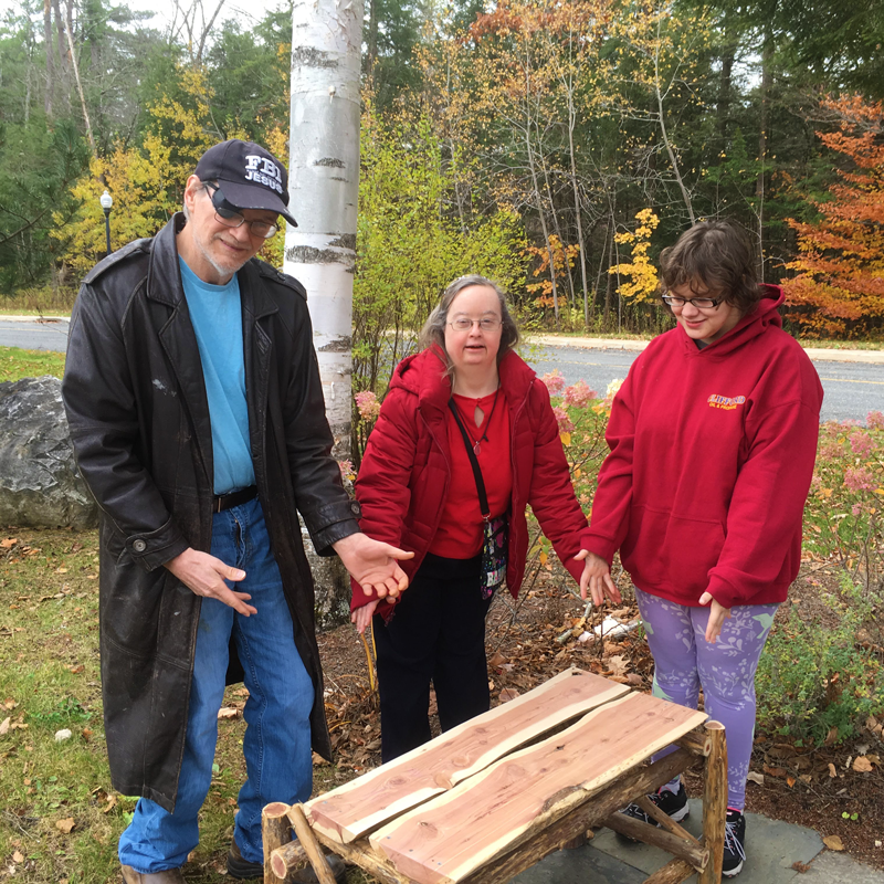A man and two women hold their hands out to show a wooden bench