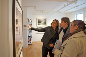 Three people look and talk about a large framed photo in an art gallery