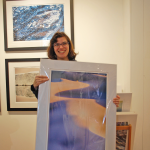 A woman smiles and holds a large photograph of sand dunes