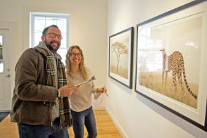 A man and woman smile while looking at a large framed photograph of a lion
