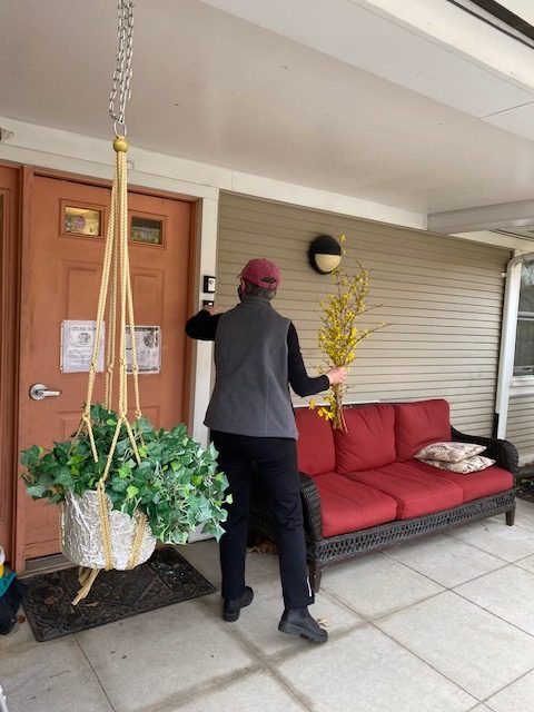 A woman rings a doorbell to deliver flowers