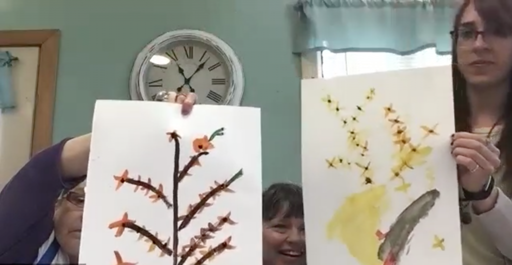Three people hold up watercolor paintings of flowers.