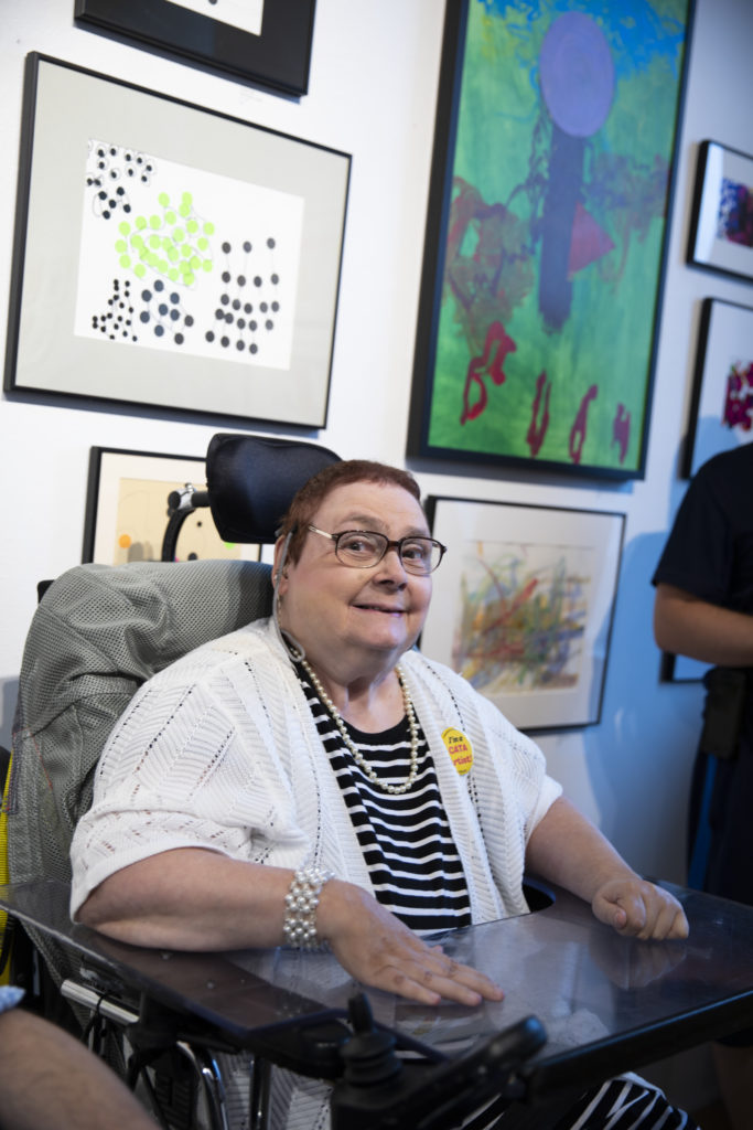 White woman in a wheelchair in a white seater and black and white striped shirt, smiles in front of a painting.