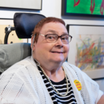 White woman in a wheelchair wearing a black and white shirt, white sweater, pearls, glasses, and smiling.