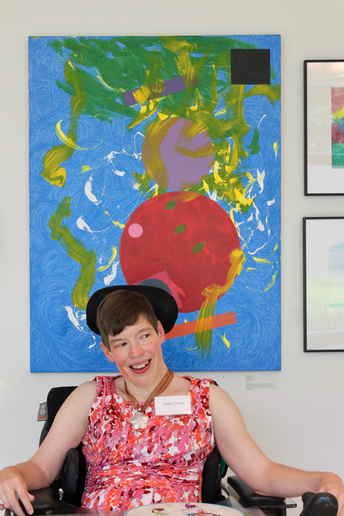 White woman in a wheelchair, smiling, wearing a pink and white floral dress. Behind her is a painting.
