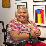 Woman of color in a wheelchair wearing a frilly tye-dyed pink and brown shirt, smiling.