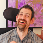 White man in a wheelchair wearing a grey striped shirt with a goatee smiling.