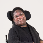 Black woman in a wheelchair wearing a black sweater, glasses, and smiling