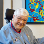 White woman in a wheelchair, wearing a light blue sweater, glasses, smiling