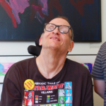 White man in wheelchair, wearing a brown shirt and glasses, smiling.