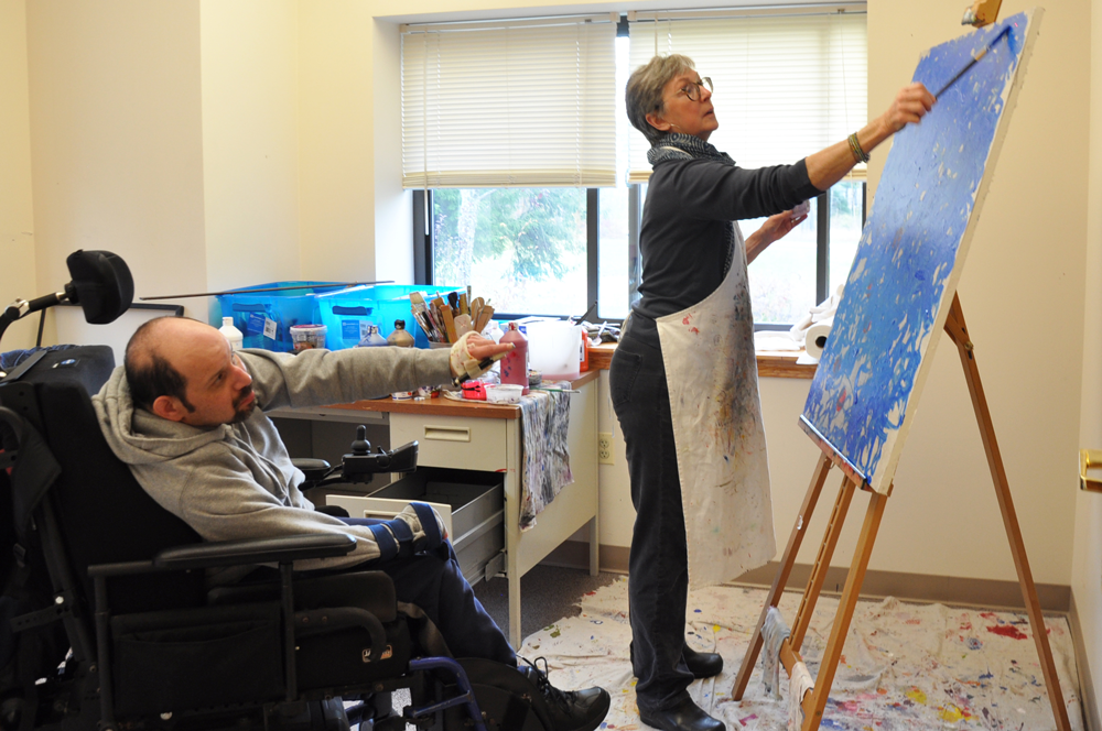 A white man in a wheelchair extends his arm to point a laser pointer towards a canvas. A woman stands at the canvas with a paintbrush.