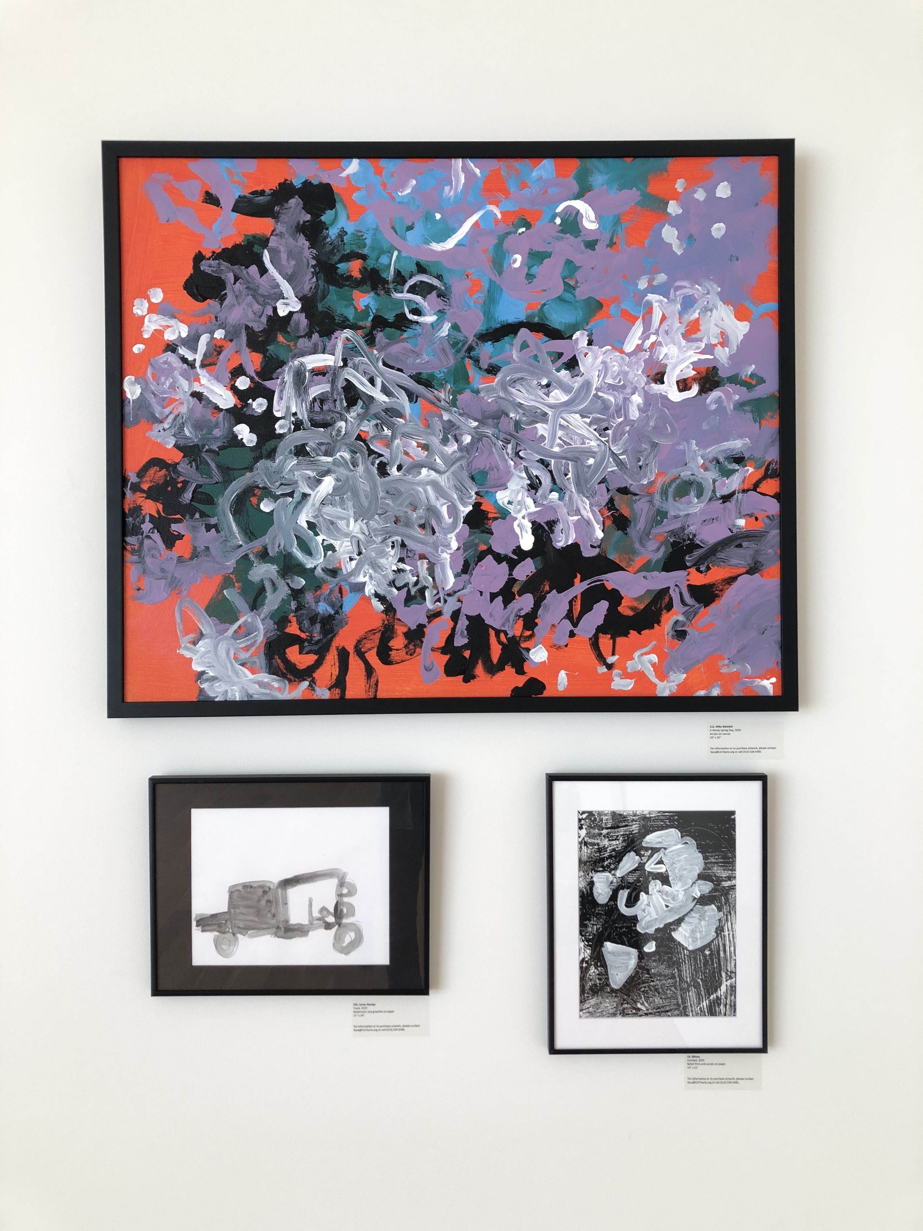 Three paintings on a wall: one large and colorful, two small black and white paintings beneath it.