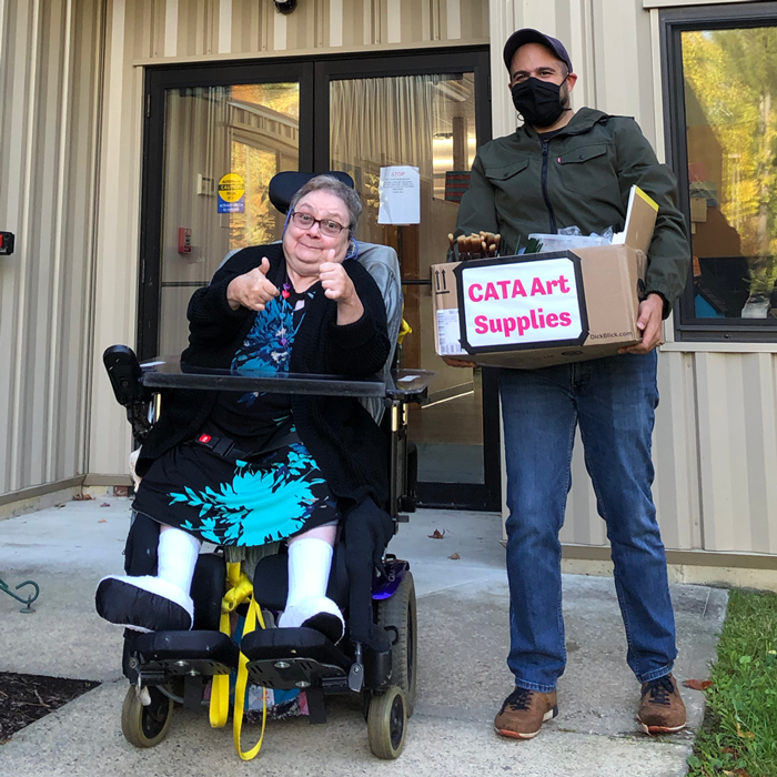 "A woman in a wheelchair gives two thumbs up next to a man holding a box reading ""CATA ART SUPPLIES"""