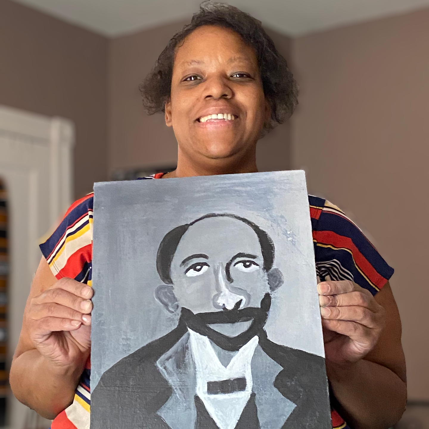 A woman smiles and holds a painting of WEB Du Bois
