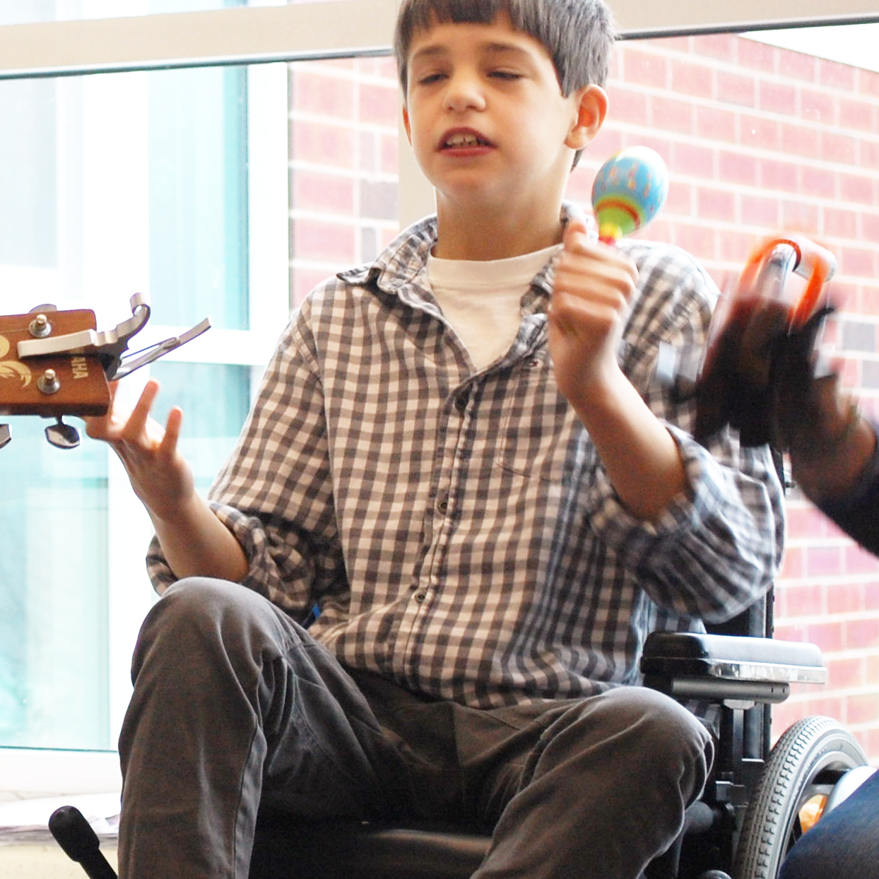 A young CATA artist in a wheelchair playing a maraca