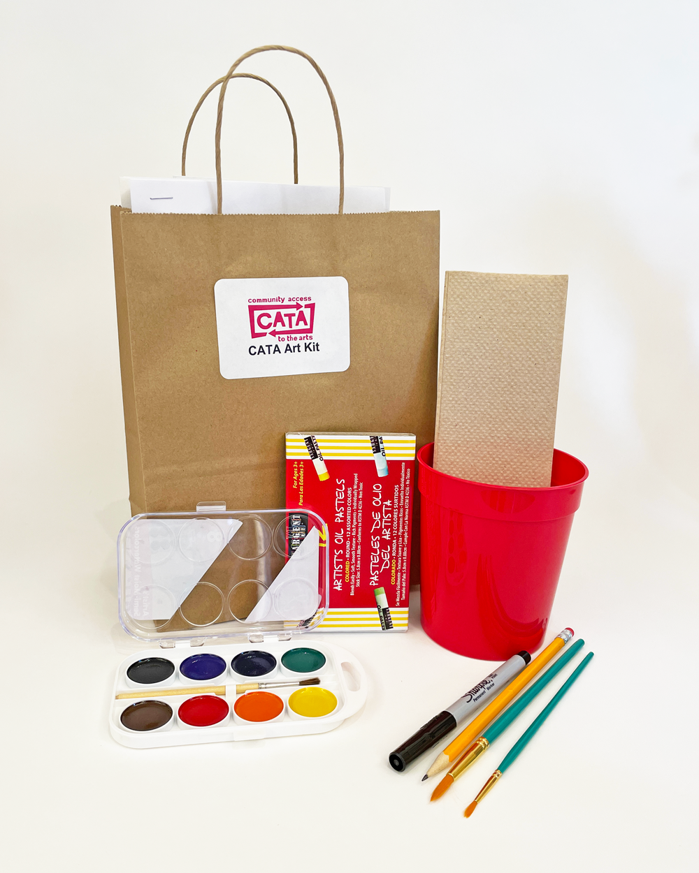 An example of a CATA art kit: a brown bag with a set of watercolor paints, paint brushes, pasels, and a red water cup.