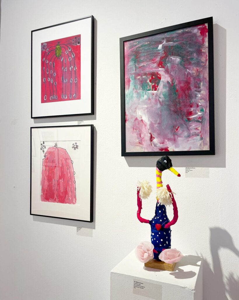 Gallery wall with three paintings and a sculpture of a duck holding pom-poms