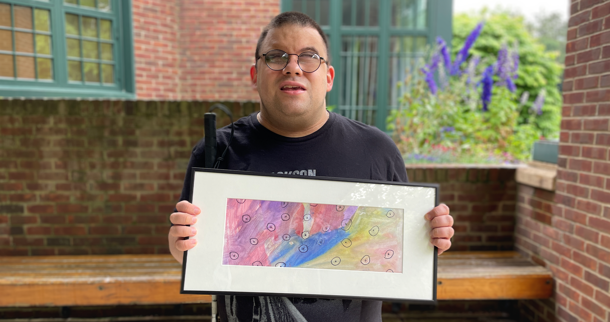 Image description: CATA artist Anthony smiles and holds his framed painting outside