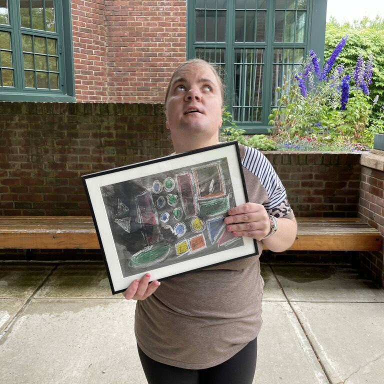 Casey stands outside holding her framed painting