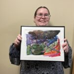Catie stands and smiles while holding her framed painting