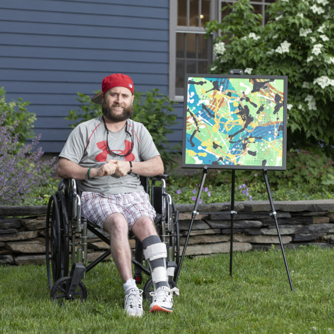 Chris sits in a wheelchair next to his painting on an easel