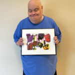David stands wearing a blue shirt and holding his framed painting