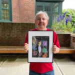 Doug stands outside in a red shirt holding his framed painting