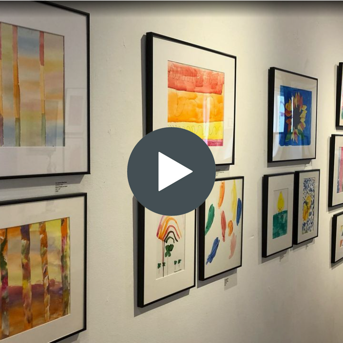 """Image of an art gallery with """"play"""" button symbol overlaid"""