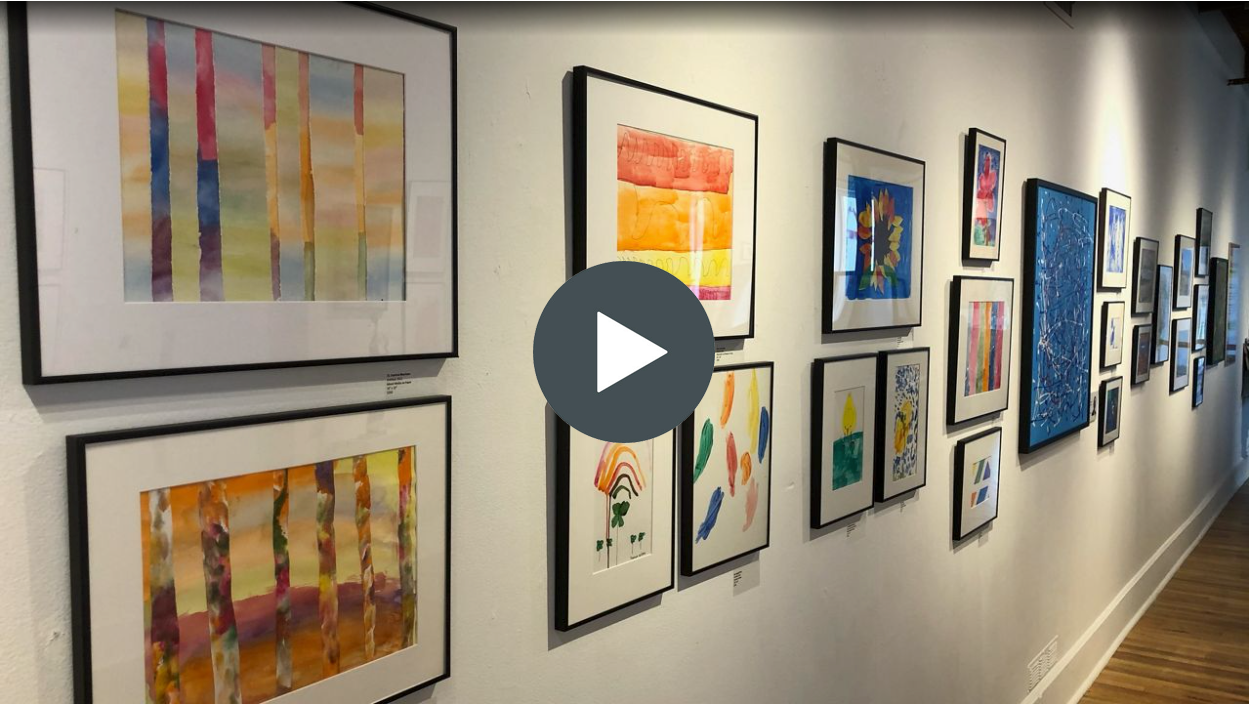 Image of an art gallery with a play button overlaid